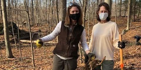 Two female volunteers holding tools and wearing masks standing in the woods