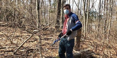 Volunteer wearing a mask holding loppers in the woods